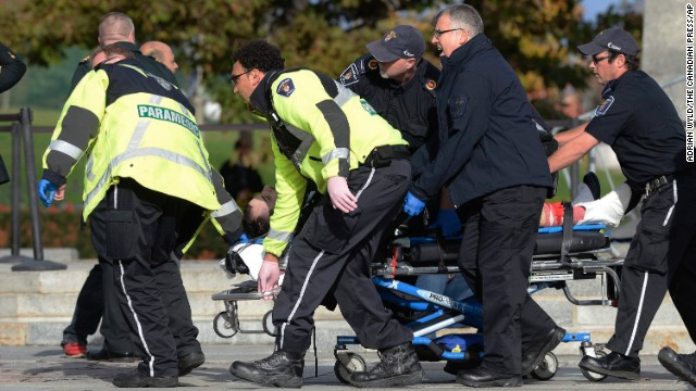 Paramedics and police pull a victim away from the Canadian War Memorial in Ottawa on Wednesday Oct. 22, 2014.  A soldier standing guard at the National War Memorial in Ottawa has been shot by an unknown gunman and people report hearing gunfire inside the halls of Parliament.  The gunman reportedly ran towards Parliament Hill, which is currently under lockdown and surrounded by security.  Prime Minister Stephen Harper was rushed away from the building to an undisclosed location, officials in his office said. (AP Photo/The Canadian Press, Adrian Wyld)