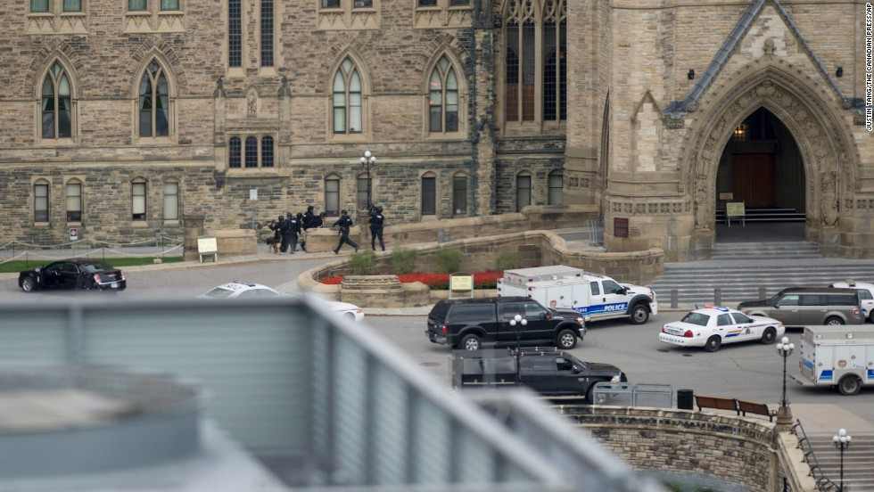 Police enter Canada's Parliament building on Wednesday, October 22, in Ottawa. A Canadian soldier was fatally shot at the National War Memorial nearby, and there were gunshots at the Parliament building itself, Ottawa police spokesman Marc Soucy said. One male suspect was also killed, police said.