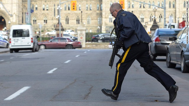 Police secure an area around Parliament Hill in Ottawa on Wednesday Oct. 22, 2014.  A soldier standing guard at the National War Memorial was shot by an unknown gunman and people reported hearing gunfire inside the halls of Parliament. Prime Minister Stephen Harper was rushed away from Parliament Hill to an undisclosed location, according to officials. (AP Photo/The Canadian Press, Adrian Wyld/The Canadian Press/AP)