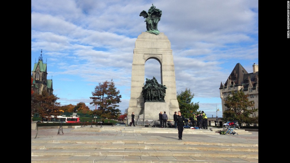 Police and medical personnel work at the scene of the shooting at the war memorial.