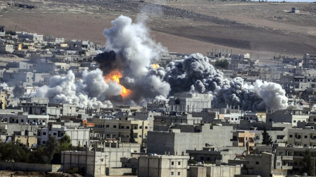 Caption:Smoke and flames billow following an explosion in the Syrian town of Kobane, also known as Ain al-Arab, from the southeastern Turkish village of Mursitpinar in the province of Sanliurfaon October 22, 2014. Turkey dropped its refusal to allow Kurdish fighters over the border to defend the besieged Syrian town of Kobane, saying it was now helping Iraqi peshmerga to cross the frontier in a major policy shift. AFP PHOTO/STRINGER (Photo credit should read STR/AFP/Getty Images)