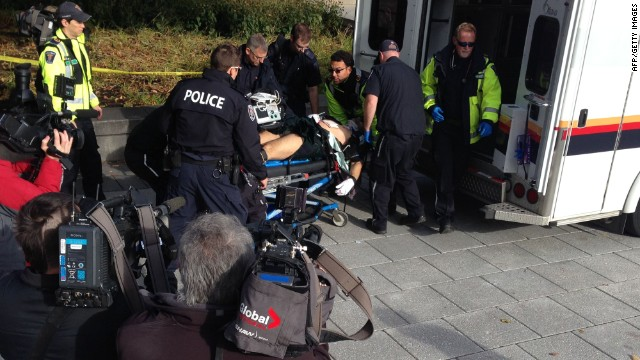 This October 22, 2014 photo shows police and medical personell moving a wounded Canadian soldier into an ambulance at the scene of a shooting at the National War Memorial in Ottawa, Canada. Parliament Hill's Centre Block is in lockdown after a Canadian soldier standing guard at the National War Memorial in Ottawa was shot by an unknown gunman and there are reports of gunfire inside the halls of Parliament. AFP PHOTO / Michel COMTEMICHEL COMTE/AFP/Getty Images