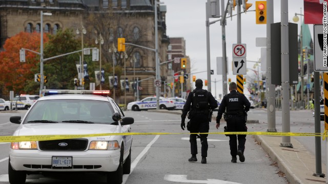 OTTAWA, CANADA - OCTOBER 22:  Ottawa police officers walk up Wellington St. near the National War Memorial where a soldier was shot earlier in the day, just blocks away from Parliament Hill, on October 22, 2014 in Ottawa, Canada. Officials are investigating multiple reports of shootings and suspects after at least one gunman shot a Canadian soldier and then entered Canada's Parliament building.   (Photo by Mike Carroccetto/Getty Images)
