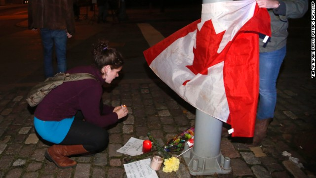 """Mourners light a candle and tie a Canadian flag around a light pole near the National War Memorial after a soldier was killed in Ottawa on Wednesday, Oct. 22, 2014. A gunman Wednesday fatally shot an honor guard at """"point blank"""" range at the National War Memorial before storming Parliament Hill. (AP Photo/The Canadian Press, Patrick Doyle)"""