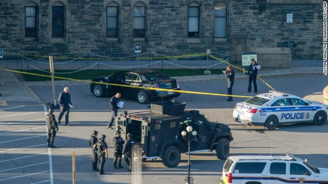 A police officer takes a photo of a vehicle, top, inside police tape outside Center Block on Parliament Hill in Ottawa, Ontario, Wednesday, Oct. 22, 2014. A gunman with a scarf over his face shot to death a Canadian soldier standing guard at the nation's war memorial Wednesday, then stormed Parliament in a hail of gunfire before he was killed by the usually ceremonial sergeant-at-arms, authorities and witnesses said. (AP Photo/The Canadian Press, Justin Tang/The Canadian Press/AP)