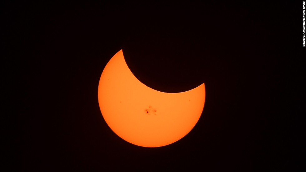 OCTOBER 24 - MT. WILSON, U.S.: Sunspots are visible on the sun during the peak moment of a partial solar eclipse. The moon, the sun and the Earth were aligned in such a way that the shadow of the moon blocked out around 34% of the sun.
