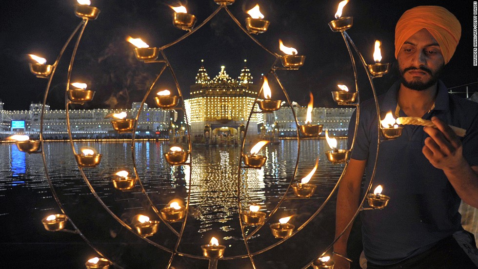 "An Indian Sikh devotee lights candles at the illuminated Golden Temple in Amritsar. Though the three faiths celebrate Diwali -- the name comes from the word Deepavali, meaning ""row of lights"" -- in different ways, the main theme symbolizes the victory of good over evil and light over darkness."