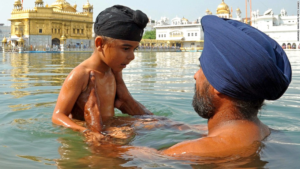 An Indian Sikh devotee holds a child as they take a dip in the holy sarover (water tank) during Bandi Chhor Divas at the Golden Temple in Amritsar.