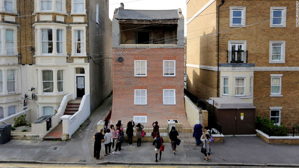 People stand outside a derelict house that Chinneck converted in Margate, England, in October 2013. Chinneck made it appear as though the front of the house was sliding away.