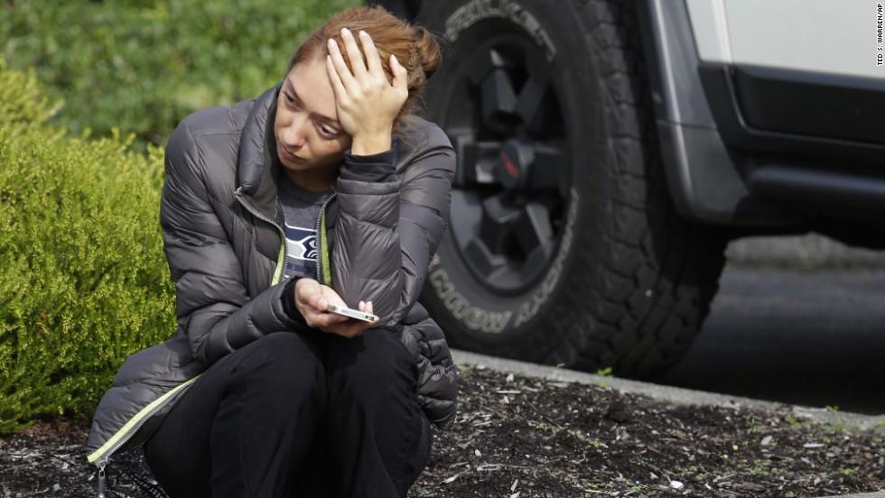 A woman waits on a curb at the church.