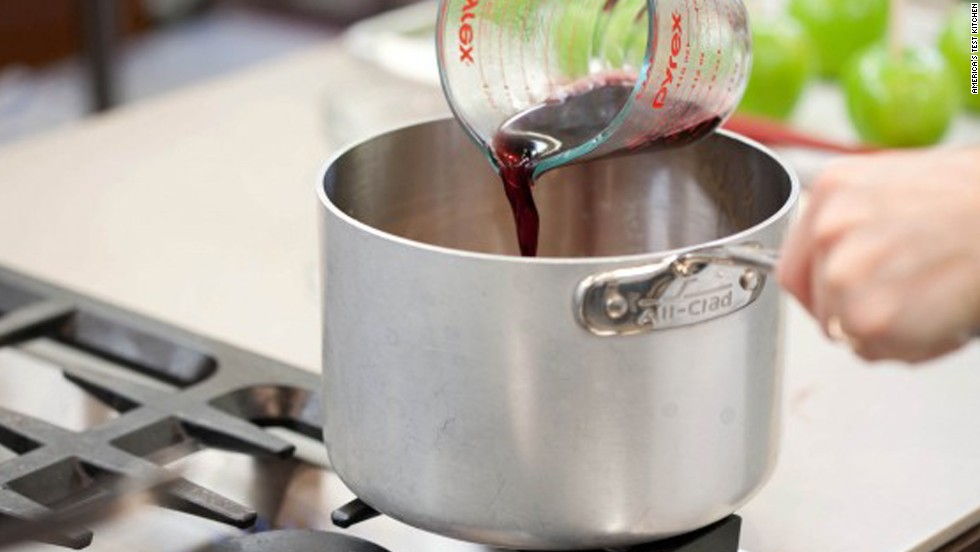 For safety's sake, remove the pan from the heat before adding the wine. There is still alcohol in the wine and you don't want to ignite it (along with a pot of boiling sugar). The mixture will bubble vigorously when you add the wine; this is normal. Return the pot back to the heat and give it a stir.