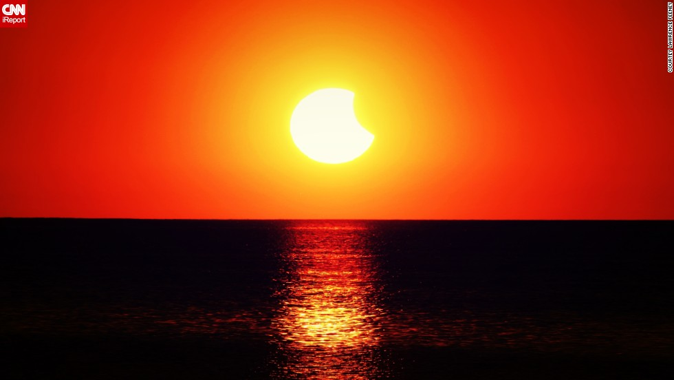 "The solar eclipse illuminates the ocean in <a href=""http://ireport.cnn.com/docs/DOC-1182916"">New Port Richey, Florida</a>."