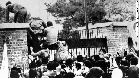 Iranian students climb over the wall of the US embassy in Tehran on November 4, 1979.