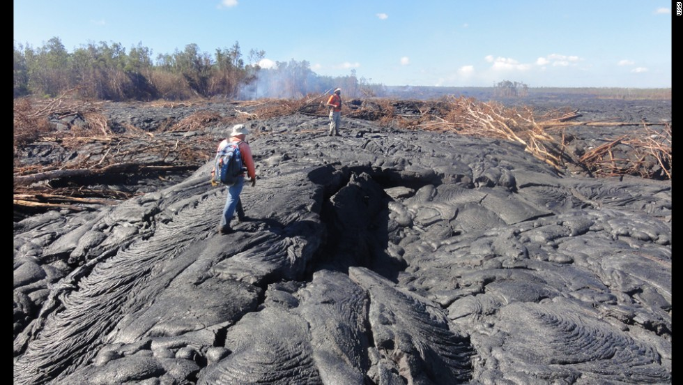 Hawaiian Volcano Observatory geologists walk over the surface of the flow to track surface breakouts along a portion of the flow margin, about a kilometer (0.6 miles) up the slope from the flow front, on October 24.