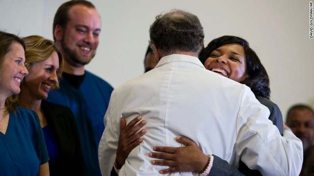Amber Vinson, 29, the Dallas nurse who was being treated for Ebola, right, embraces Emory University Hospital epidemiologist Dr. Bruce Ribner, as she leaves a press conference after being discharged from the hospital, Tuesday, Oct. 28, 2014, in Atlanta. Vinson worked as a nurse at Texas Health Presbyterian Hospital Dallas and cared for Thomas Eric Duncan, a Liberian man who died of Ebola at the hospital on Oct. 8. Vinson was one of two nurses who became infected while caring for Duncan. (AP Photo/David Goldman)