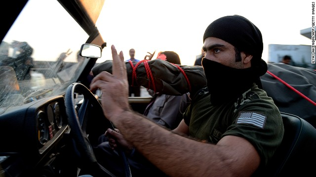 A peshmerga fighter flashes victory sign as their convoy arrives at the Habur crossing along the Turkish-Iraqi border with heavy weapons on October 29, 2014.