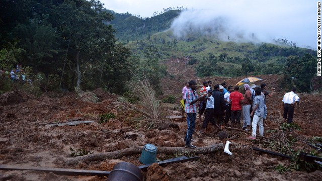 :Sri Lankan residents stand at the site of a landslide caused by heavy monsoon rains in Koslanda village in central Sri Lanka on October 29, 2014.