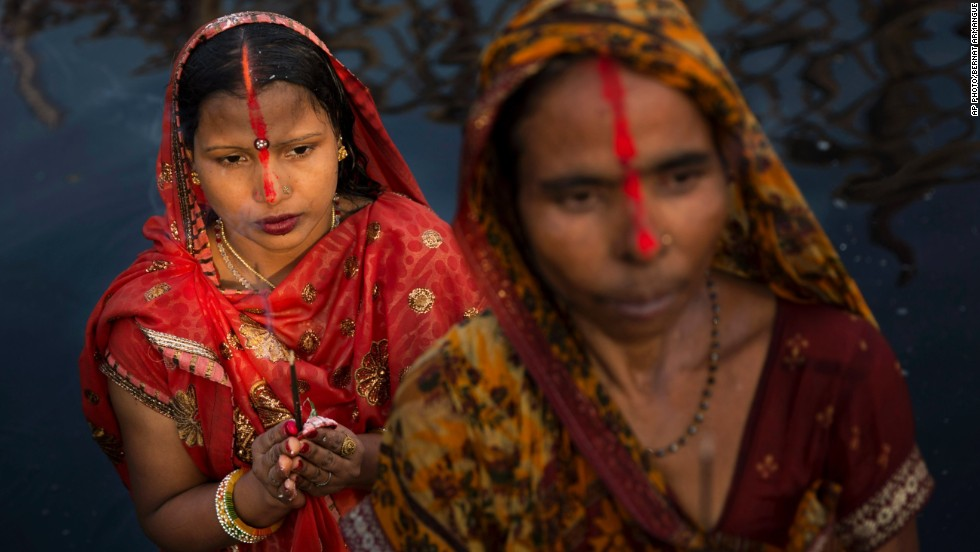 OCTOBER 30 - NEW DELHI, INDIA:  Hindu women with vermillion powder on their foreheads perform rituals at sunset to mark Chhath Puja festival. Chhath is an ancient Hindu way of thanking the Sun God for sustaining life on Earth.