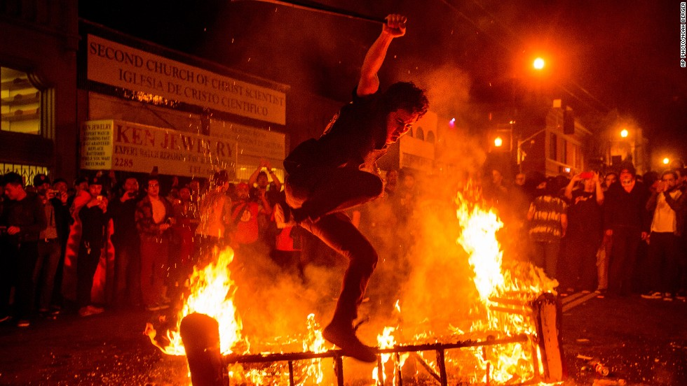 OCTOBER 31 - SAN FRANCISCO, U.S.: A man jumps over a burning couch as fans celebrate after the San Francisco Giants beat the Kansas City Royals to win the World Series -- for the third time in five years.