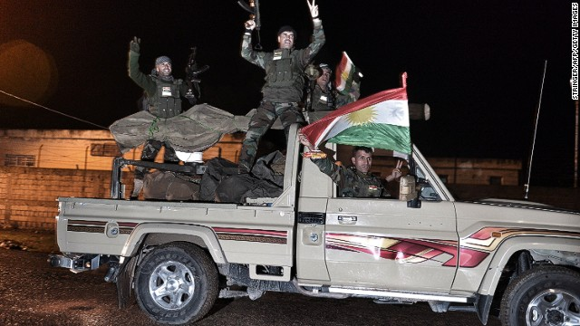Kurdish peshmerga fighters gesture and wave a Kurdish flag from a military vehicle armed with a heavy infantry weapon as they ride towards the Syrian town of Kobane, also known as Ain al-Arab, from the border town of Suruc, in the Turkish southeastern Sanliurfa province, on October 31, 2014. Kurdish peshmerga reinforcements entered Syria from Turkey late on October 31 to bolster defenders in the key border town of Kobane which is under assault by Islamic State group jihadists. AFP PHOTO/STRINGER (Photo credit should read STRINGER/AFP/Getty Images)