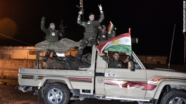 Kurdish peshmerga fighters gesture and wave a Kurdish flag from a military vehicle armed with a heavy infantry weapon as they ride towards the Syrian town of Kobane, also known as Ain al-Arab, from the border town of Suruc, in the Turkish southeastern Sanliurfa province, on October 31, 2014.