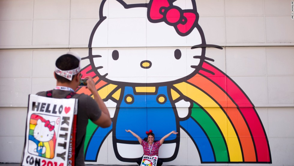 Keith Nunez, left, takes pictures of his wife, Carolina, in front of a Hello Kitty mural on Thursday, October 30. The first Hello Kitty fan convention was held to honor the character's 40th birthday. The event takes place in Los Angeles and runs from October 30 to November 2.