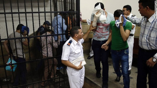Men accused of being in a same-sex wedding video shield their faces Saturday in a Cairo courtroom.
