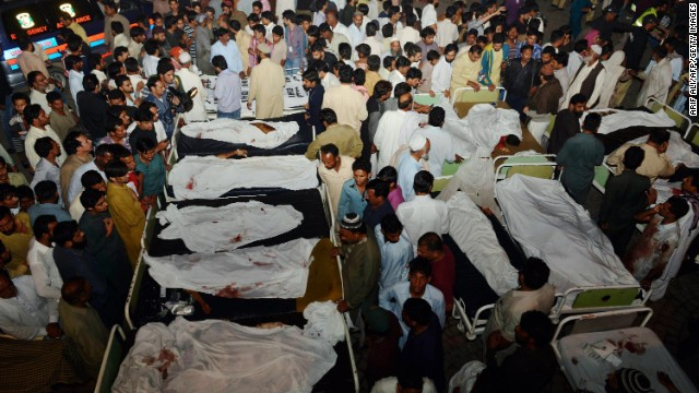Pakistani relatives gather around the bodies of blast victims after a suicide bomb attack Sunday near the Pakistan-India border.