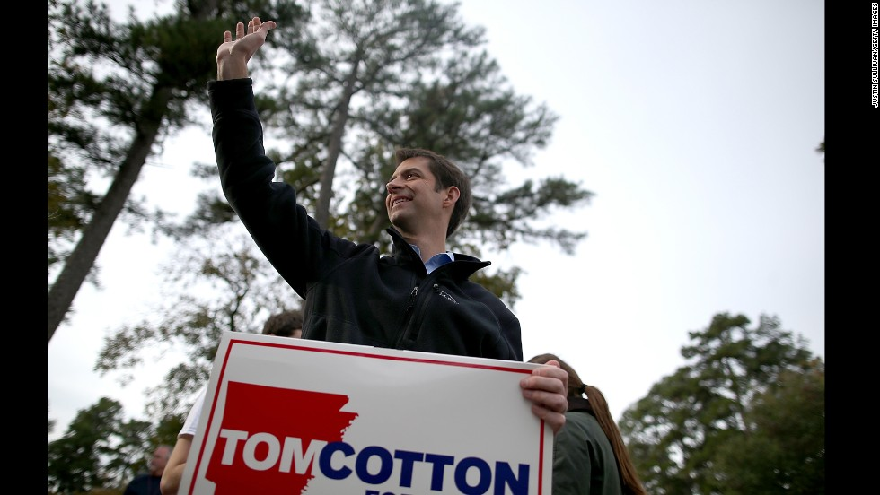 Cotton waves to people entering a polling place in Little Rock on November 4.