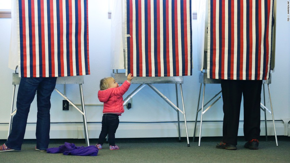 Zoe Buck checks out an empty voting booth as her mother, Julie, votes at the Alaska Zoo polling place in Anchorage.