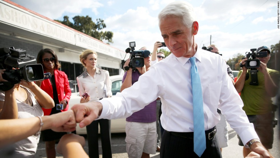 Crist bumps fists with a supporter as he makes an Election Day visit to thank volunteers at the Total Image Hair Salon in Tampa, Florida.