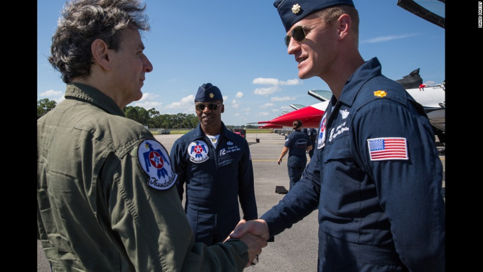 Maj. Michael Fisher shakes hands with CNN's Carl Lavin before the air show on October 9. Also on the flight line is Maj. Darrick Lee, Thunderbirds public affairs officer.