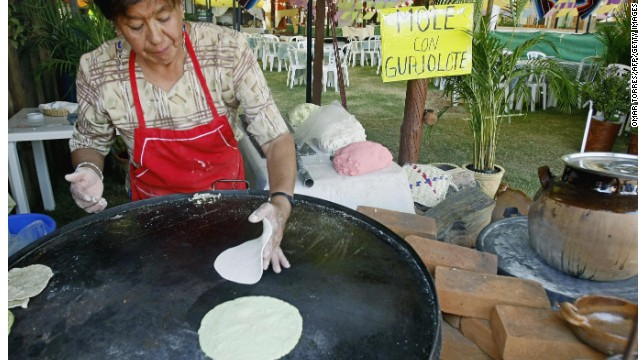 Maria Alejandra cooks Mexican tortillas on the 'comal' ( metal hotplate for cooking them) at one of the restaurants offering 'mole' with turkey 01 October, 2007 at the Mole Fair in San Pedro Atocpan, near Mexico City's inner limits. The mole, a sauce of pre-hispanic origin made out of 26 basic ingredients cooked according to traditional recipes, like four different types of chili, almonds, nuts, and chocolate transmitted through generations, is a valued jewel of the town's culinary. Every year the inhabitants of San Pedro Atocpan (fertile land, in Nahutal), 92 percent of whom work making and selling mole, gather for the gastronomic fair. AFP PHOTO/Omar TORRES (Photo credit should read OMAR TORRES/AFP/Getty Images)