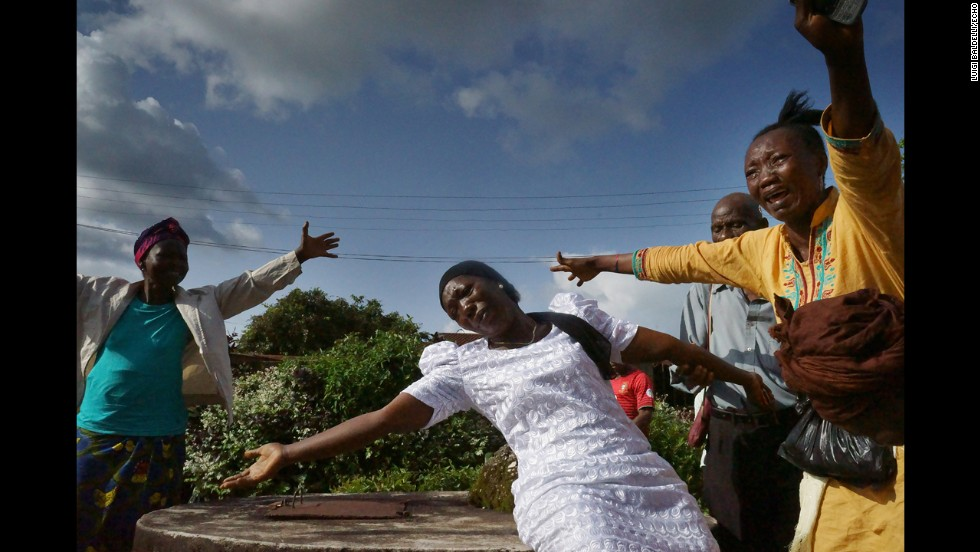 The wife of a man who died from ebola mourns during his funeral. (Luigi Baldelli/ECHO)