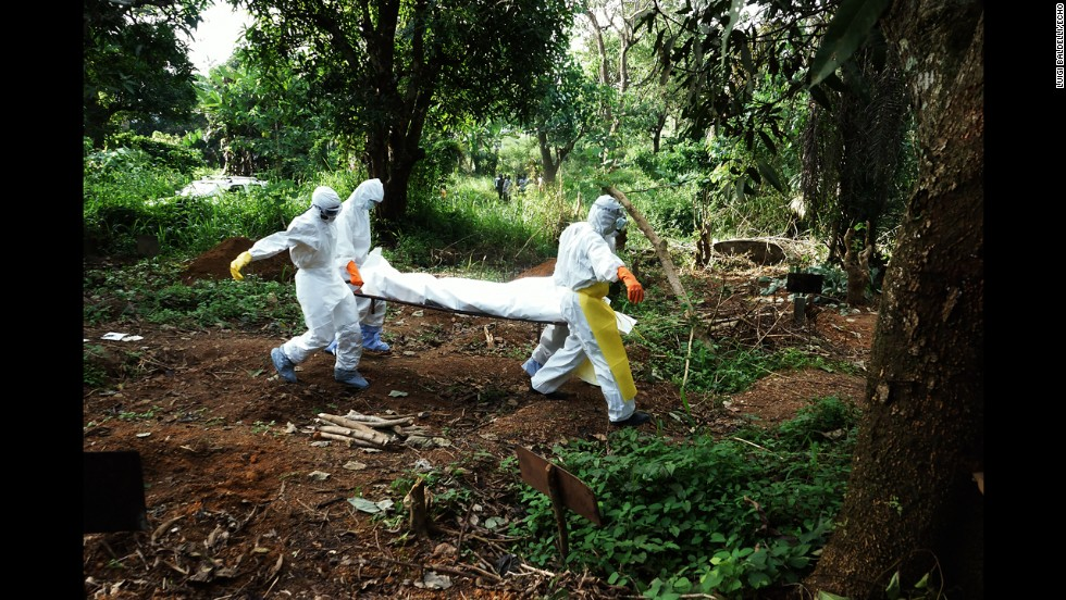 Health workers carry the body of a person who died from ebola to the cemetery. (Luigi Baldelli/ECHO)