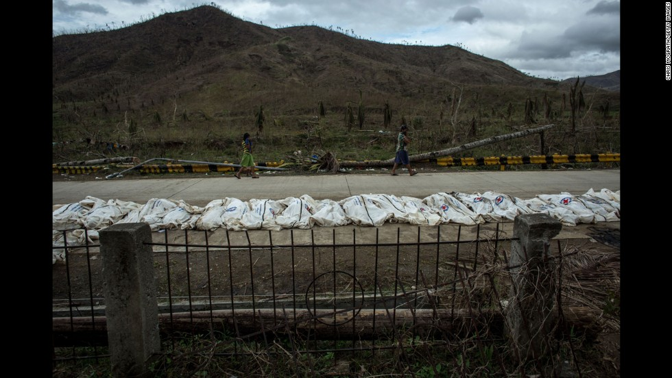 Bodies are seen on a road before being placed in a mass grave on the outskirts of Tacloban City on November 20, 2013.