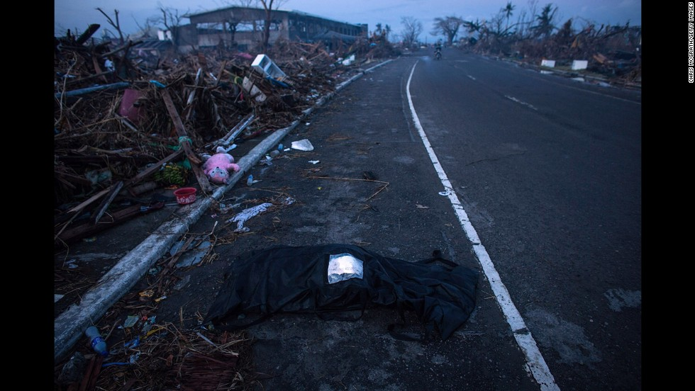 A body waits to be collect on the side of the road in Tacloban City on November 14, 2013.
