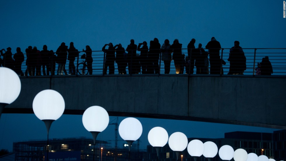 People look at balloons of the art project Lichtgrenze (Border of Light) in Berlin.