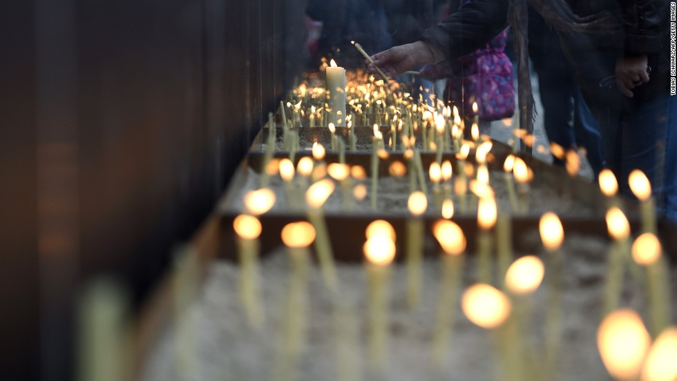 People light candles at the National Memorial for the Victims of the Berlin Wall during the commemorations.