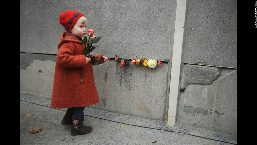 Hulda, age 3, places flowers between blocks of the former Berlin Wall.