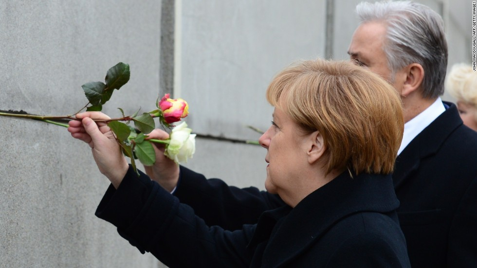 German Chancellor Angela Merkel and Berlin Mayor Klaus Wowereit place roses in the preserved segment of the wall.