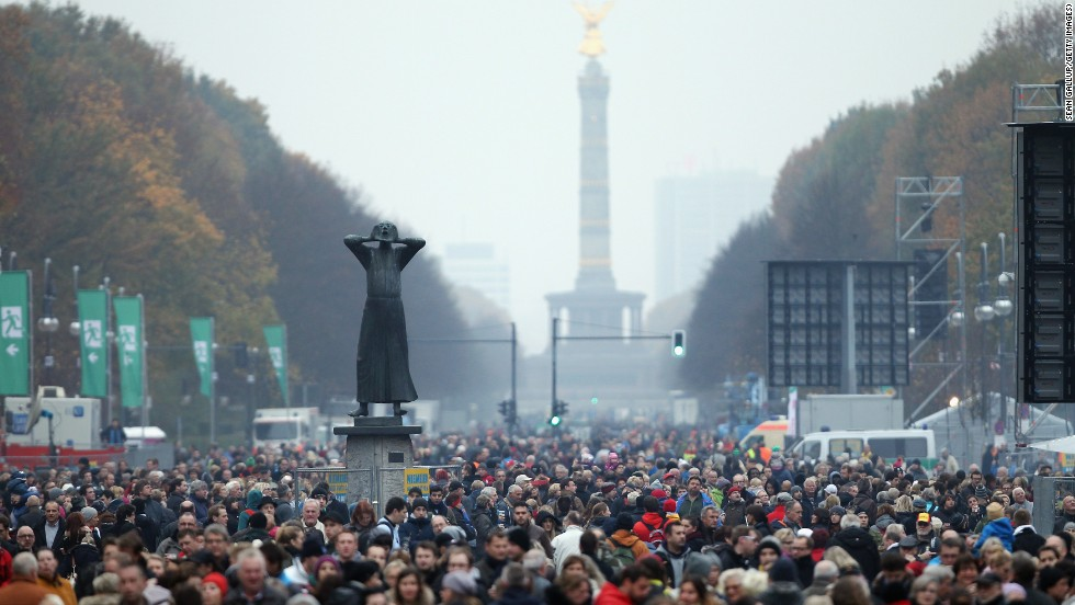 "A statue called ""Der Rufer"" (""The Caller""), who is yelling to the east demanding freedom, stands over crowds gathered to celebrate the anniversary."