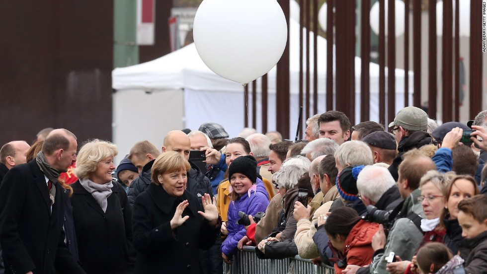 Merkel and other officials greet spectators as they walk to the Chapel of Reconciliation behind a section of the former Berlin Wall.
