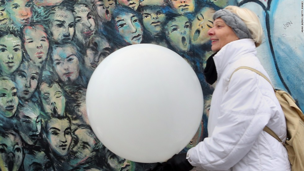 A visitor carries a balloon from the Lichtgrenze light installation.