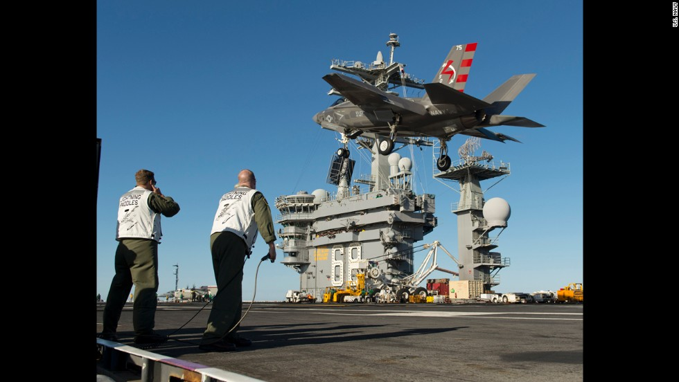 An F-35C passes over the deck of the USS Nimitz during testing.