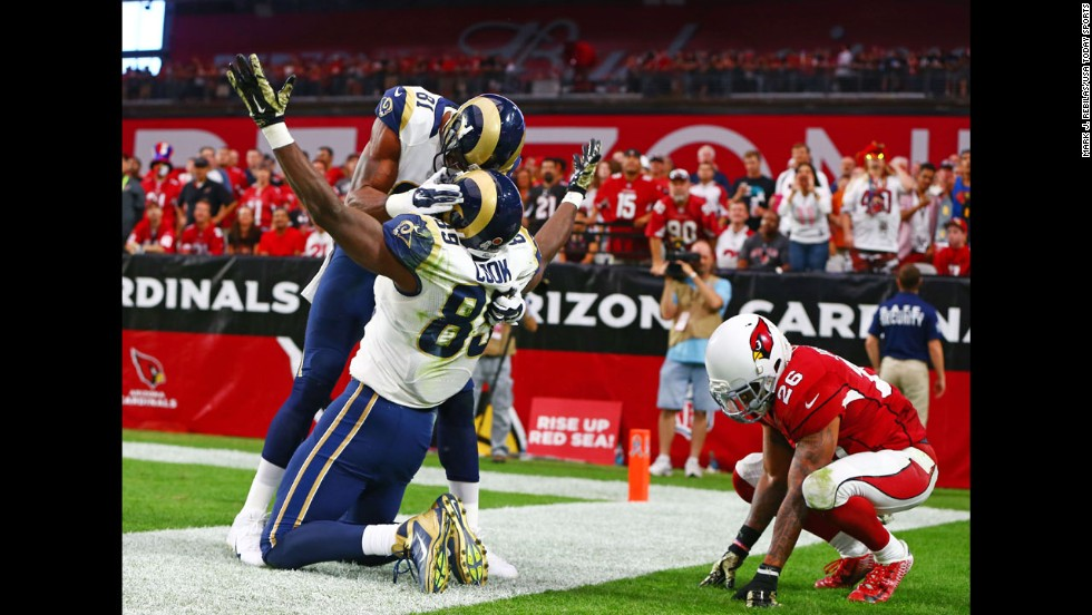 St. Louis Rams tight end Jared Cook celebrates his touchdown catch with wide receiver Kenny Britt as Arizona Cardinals safety Rashad Johnson reacts in the second quarter at the University of Phoenix Stadium in Glendale, Arizona, on Sunday, November 9. Arizona won 31-14.