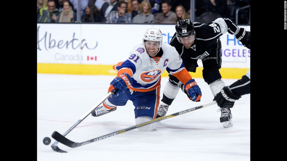 John Tavares of the New York Islanders reaches for the puck with Jarret Stoll of the Los Angeles Kings during the third period at Staples Center in Los Angeles on Thursday, November 6. The Islanders won 2-1.
