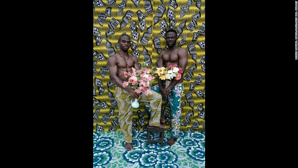 Bodybuilders pose with flowers against a colorful backdrop.