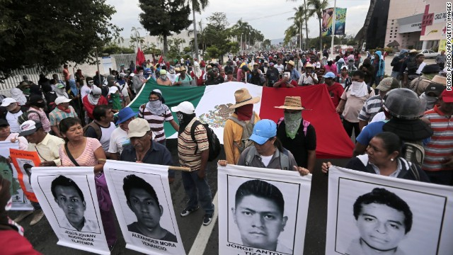 Students, peasants and other people demonstrate against the suspected massacre of 43 missing Mexican students, in the proximities of Acapulco's airport, in the Mexican state of Guerrero State, on November 10, 2014. Protesters angry at the suspected massacre threw stones and a firebomb at riot police in the Pacific resort of Acapulco on Monday, injuring 11 officers. Around 300 students, some wearing masks and armed with sticks and machetes, were joined by some parents of the 43 missing young men as they marched toward the city's airport, but police blocked their way. Mexico was confronted with one of the grisliest massacres in years of drug violence after gang suspects confessed to slaughtering 43 missing students and dumping their charcoaled remains in a river.   AFP PHOTO/PEDRO PARDO        (Photo credit should read Pedro PARDO/AFP/Getty Images)