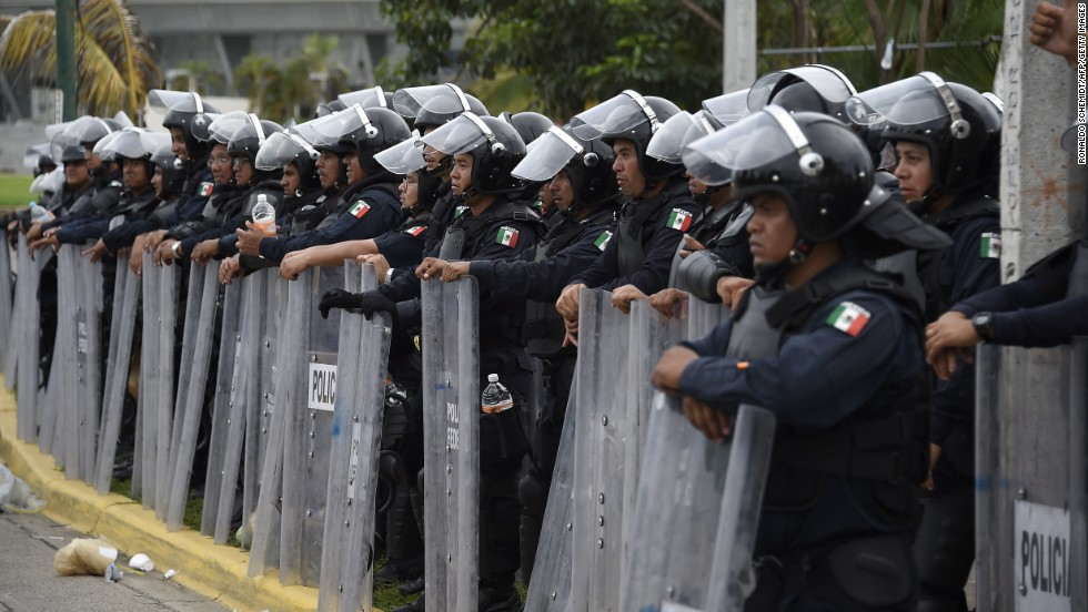 Riot police stand guard near the airport in Acapulco on November 10.